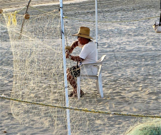 This fisherman works day after day patiently repairing his nets.  A;sways fun to see him bring them in and see what the ocean shared with him.