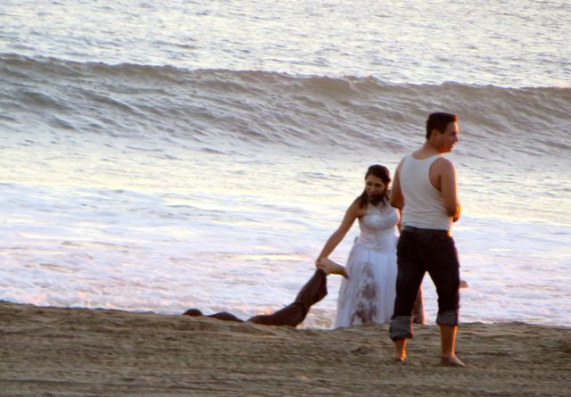 Mexican photographers like to create drama.  Both the bride and groom are already wet form the high surf.  Here the photographer in the white top jas the groom laying in the beach with the bride pullinj gat his leg.....she is rescuing her husband!!